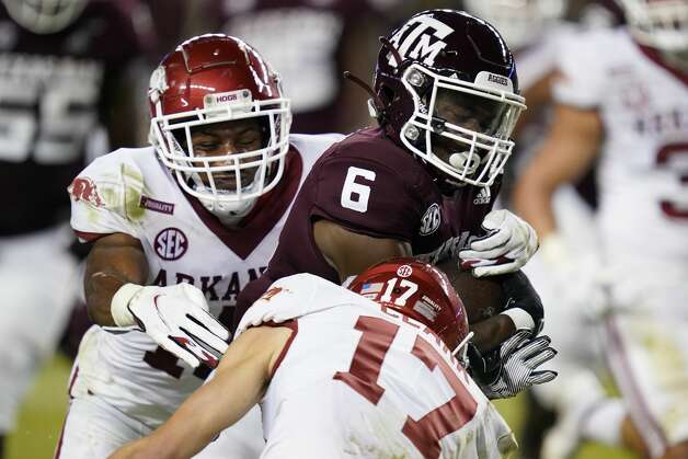 Texas A&M running back Devon Achane (6) breaks a tackle by Arkansas defensive back Hudson Clark (17) during a 30-yard touchdown run against during the second half of an NCAA college football game, Saturday, Oct. 31, 2020, in College Station, Texas. (AP Photo/Sam Craft) Photo: Sam Craft/Associated Press / Copyright 2020 The Associated Press. All rights reserved.