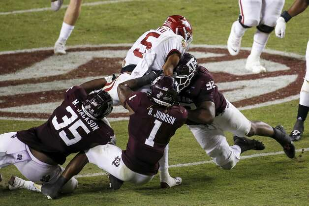 COLLEGE STATION, TEXAS - OCTOBER 31: Rakeem Boyd #5 of the Arkansas Razorbacks is tackled by Buddy Johnson #1 and Jayden Peevy #92 of the Texas A&M Aggies in the third quarter at Kyle Field on October 31, 2020 in College Station, Texas. (Photo by Tim Warner/Getty Images) Photo: Tim Warner/Getty Images / 2020 Getty Images