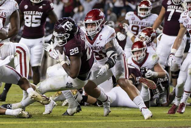 Texas A&M running back Isaiah Spiller (28) rushes for a touchdown against Arkansas linebacker Grant Morgan (31) during the second quarter of an NCAA college football game Saturday, Oct. 31, 2020, in College Station, Texas. (AP Photo/Sam Craft) Photo: Sam Craft/Associated Press / Copyright 2020 The Associated Press. All rights reserved.