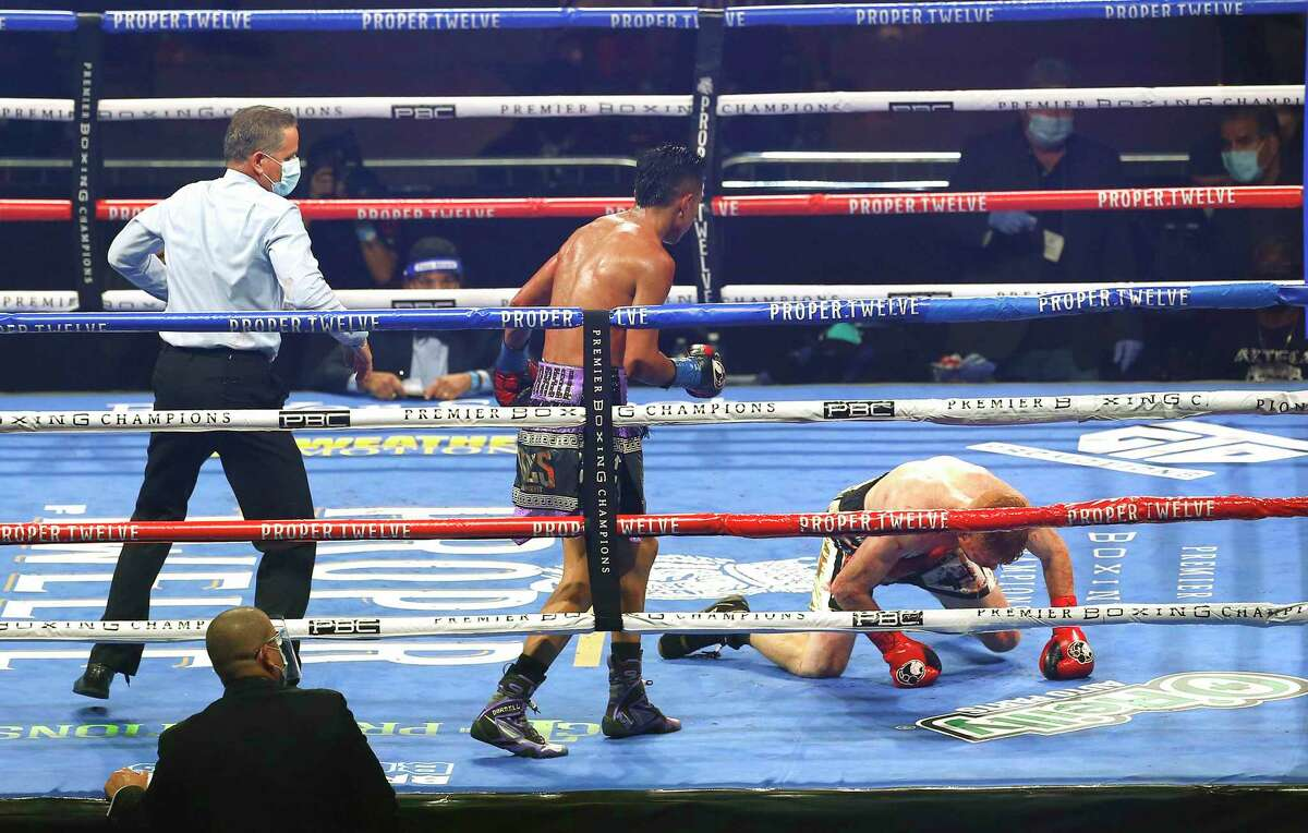 San Antonio's Mario Barrios, left, watches as he drops Ryan Karl in the sixth round of their WBA junior middleweight bout Oct. 31 at the Alamodome.