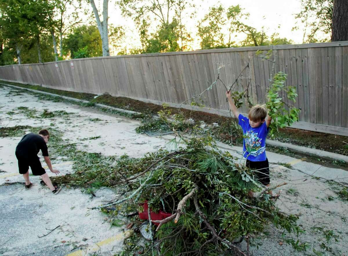 Gavin Seaton, 7, loads up a wagon with his brother, Hunter Fregia, 8, as they clean up the parking lot of their apartment complex in Orange, Texas, following Hurricane Laura on Thursday, Aug. 27, 2020.