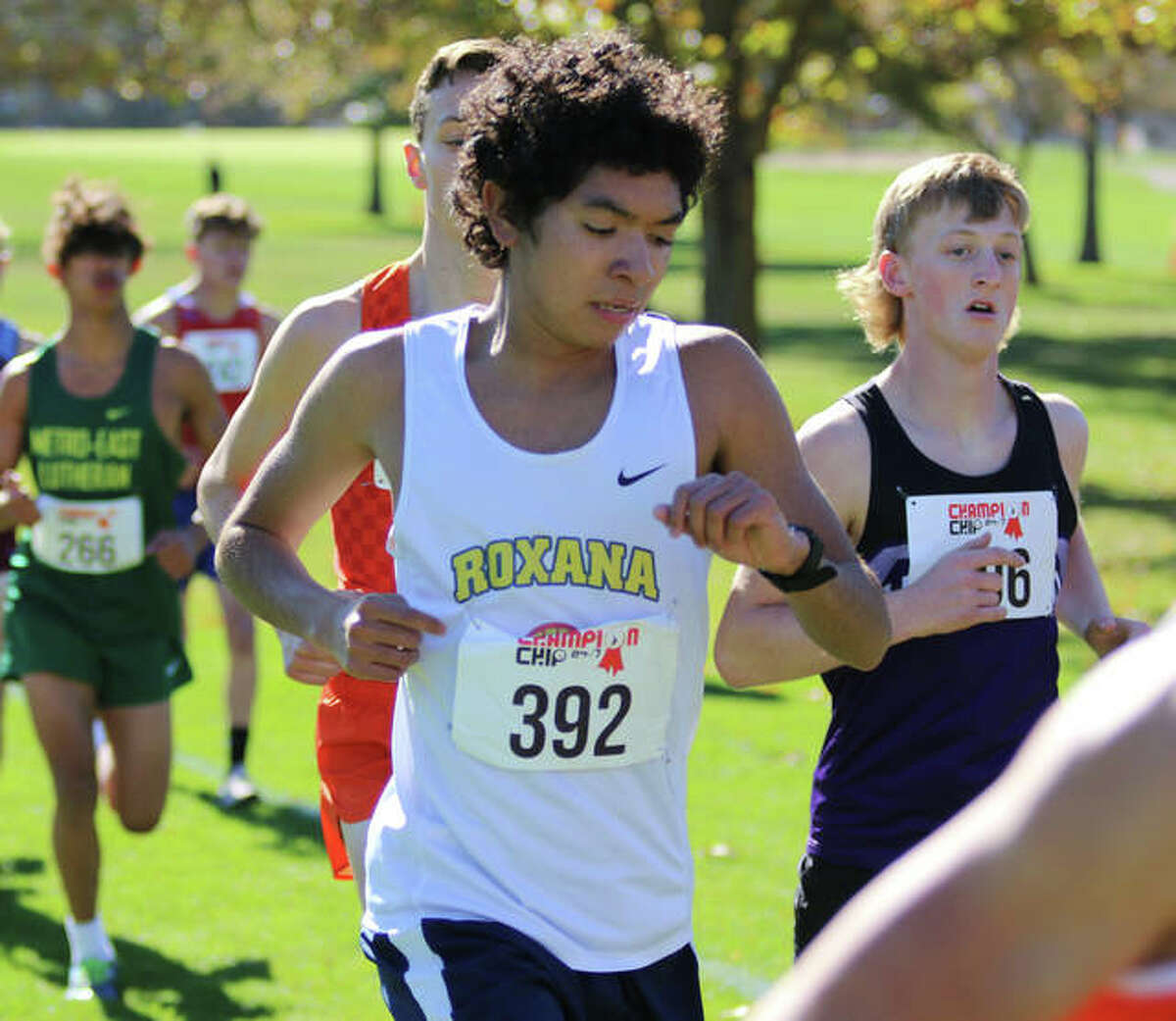 Roxana's Carlos Ruvalcaba checks his watch early in the race at the Decatur St. Teresa Class 1A Sectional on Saturday at Hickory Point golf course in Forsyth. Ruvalcaba placed seventh.