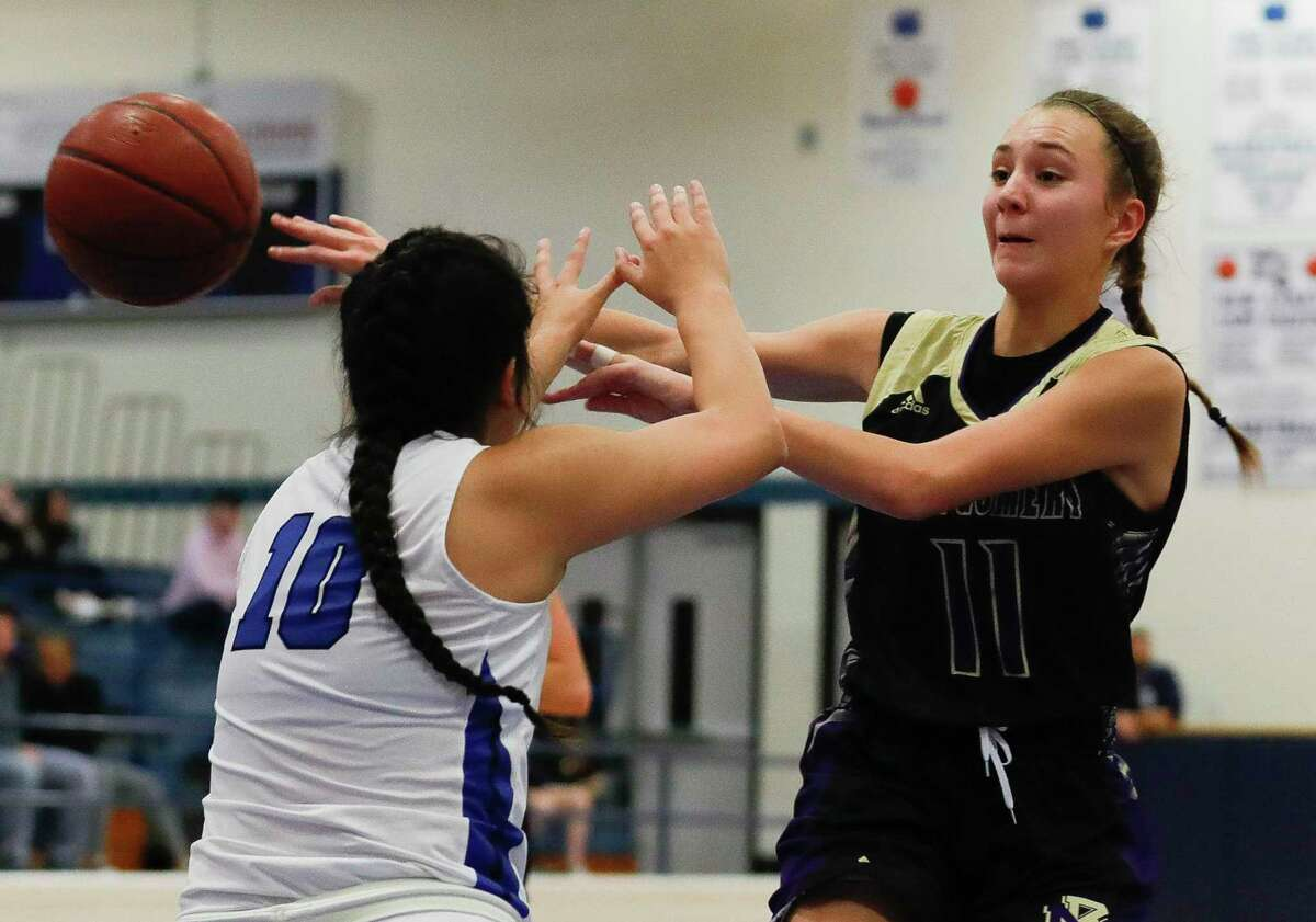 Montgomery power forward Regan Van Dyne (11) makes a pass to center Marie Geppelt as New Caney small forward Valarie Gonzales (10) defends during the first quarter of a District 20-5A high school basketball game at New Caney High School, Tuesday, Dec. 10, 2019, in New Caney.