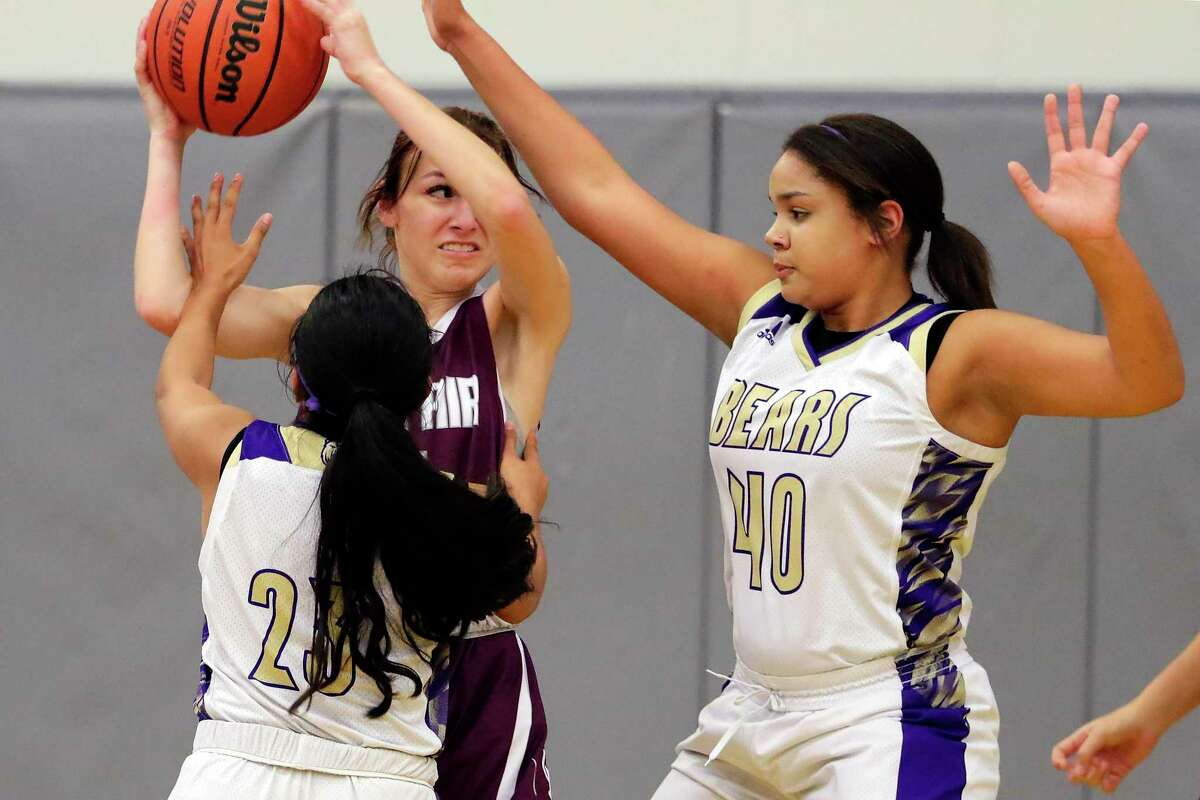 Cy-Fair's Peyton Gerold looks to pass the ball under pressure from Montgomery's Jade Gomez (23) and Jelena Ward (40) during the first half of their high school basketball game Tuesday, Nov. 19, 2019 in Montgomery, TX.