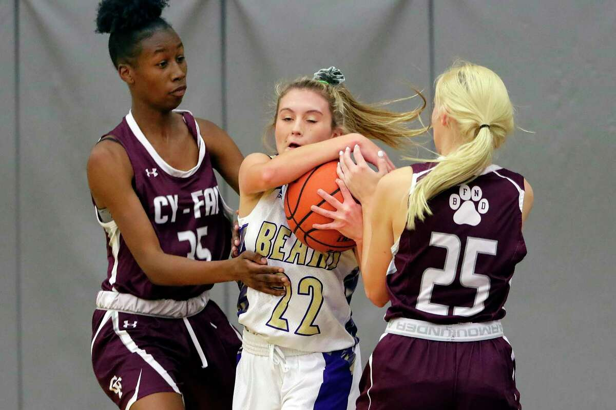Montgomery's Chloe Good (22) battles to keep the ball from Cy-Fair's Aladrian Fleming (35) and Paige Gerold (25) during the first half of their high school basketball game Tuesday, Nov. 19, 2019 in Montgomery, TX.