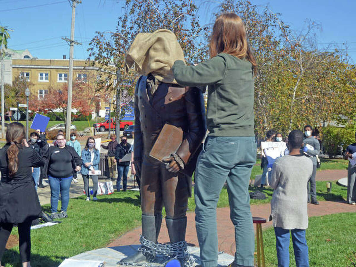 Eden Vitoff, one of the organizers of Saturday's Black Lives Matter protest to remove the Ninian Edwards statue in downtown Edwardsville, puts chains and a burlap sack on the statue near the end of the event.