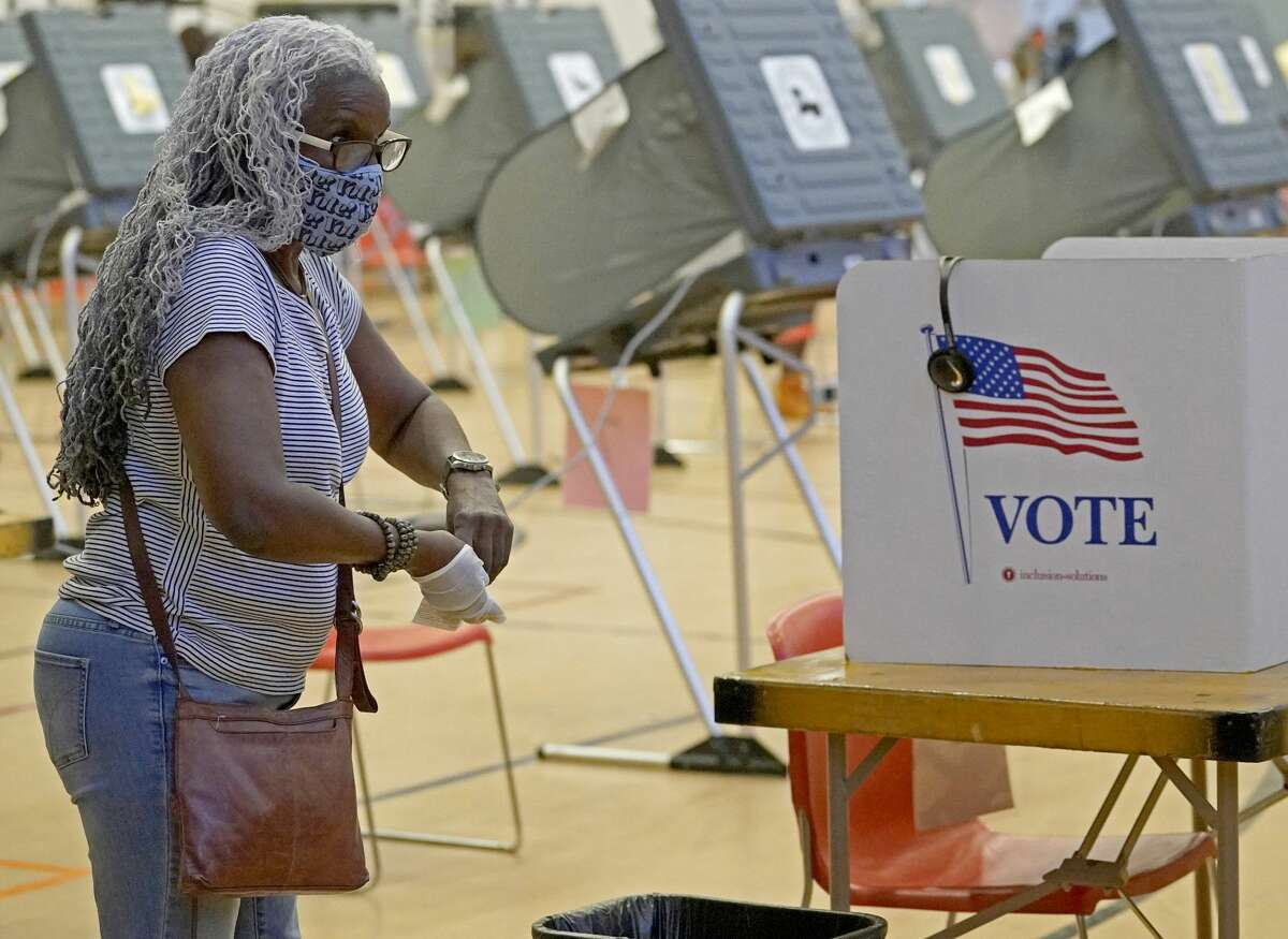 A voter takes off gloves after voting at the Metropolitan Multi-Services Center, 1475 W. Gray St.
