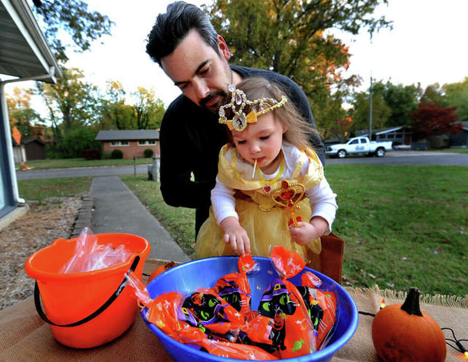 Francesca Franklin Fisher, 2, of Edwardsville, gets a boost from her father Josh Fisher as she reaches for Halloween candy while trick or treating in Edwardsville Saturday. Photo: Thomas Turney | For The Intelligencer