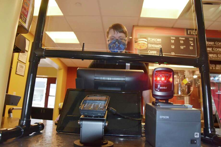 Corey Fisher can be seen at one of the registers at the Vogue Theatre which now has changed certain operations like having credit card readers available in front and face shields at registers among other changes. (Arielle Breen/News Advocate)