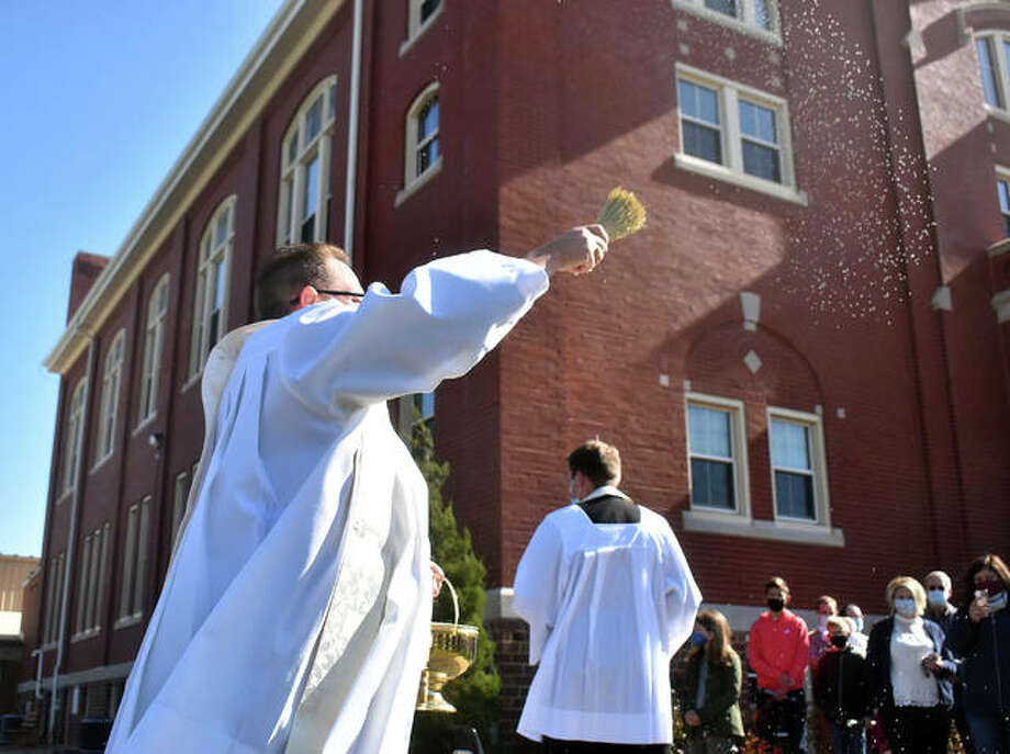 St. Boniface Pastor Fr. Jeff Goeckner tosses holy water into the air as he blesses the ground that will be used for the new gymnasium/parish center on the campus of St. Boniface Catholic Church.