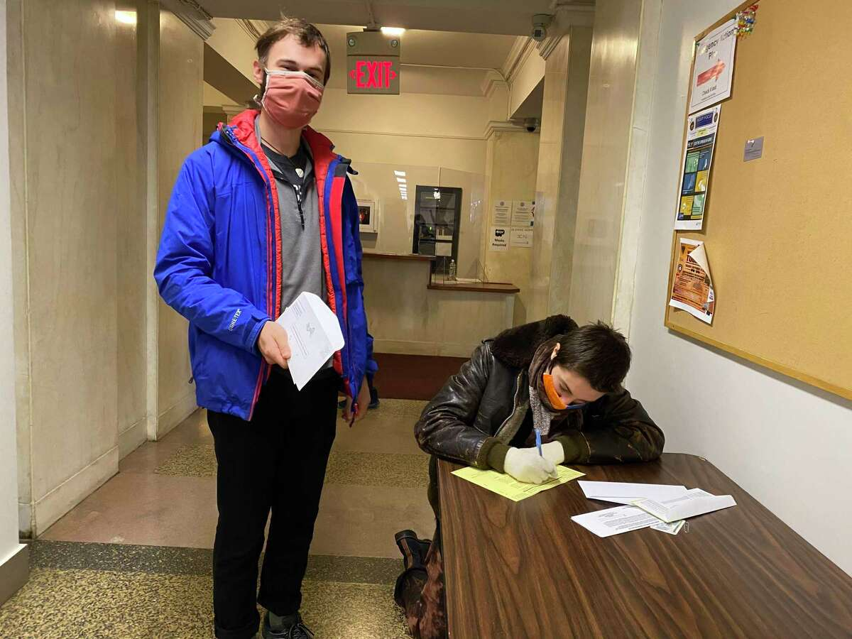Aidan Pillard and Jax Blaska fill out absentee ballots Sunday at the Hall of Records in order to avoid having to show up at the polls on Tuesday.