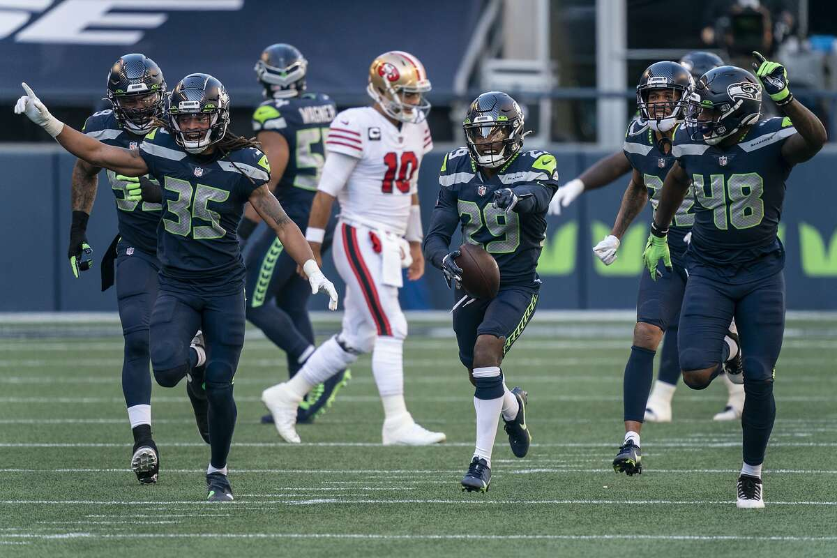 From left, Seattle Seahawks cornerback Ryan Neal, cornerback D.J. Reed and tight end/defensive end Stephen Sullivan celebrate an interception of San Francisco 49ers quarterback Jimmy Garoppolo during the first half span NFL football game, Sunday, Nov. 1, 2020, in Seattle. (AP Photo/Stephen Brashear)