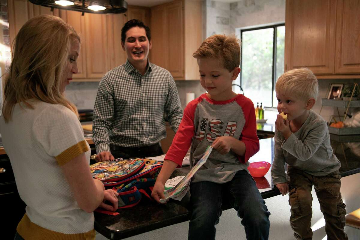 Max McGuire, 6, shows his drawing to his parents, Aubra and Ryan McGuire, as his brother, Rhett, 3, watches at their home in San Antonio on Friday. The family is among more than 11 million Americans who purchase their health insurance through the Affordable Care Act's federal and state marketplaces.