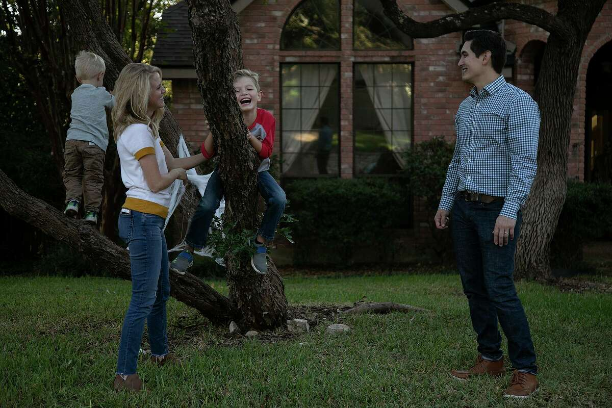 Aubra and Ryan McGuire watch as their children, Rhett, 3, and Max, 6, climb a tree outside their home in San Antonio on Friday. The family is among more than 11 million Americans who purchase their health insurance through the Affordable Care Act's federal and state marketplaces.
