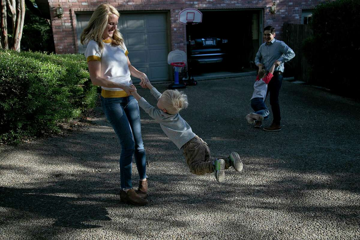 Aubra McGuire swings her son, Rhett, 3, while her husband, Ryan McGuire, swings Max, 6, upon Ryan's arrival home from work in San Antonio on Friday. The family is among more than 11 million Americans who purchase their health insurance through the Affordable Care Act's federal and state marketplaces.