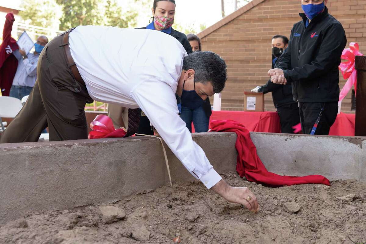 Dr. Gerardo Cruz, Assistant Superintendent for Curriculum and Instruction places a tulip bulb in the Valdez High School flower bed.