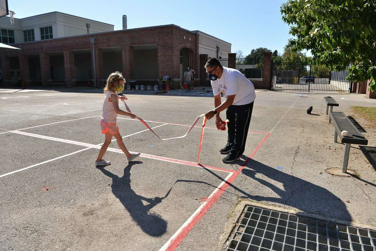 Raul Salazar helps Moira McNeel pull tape from a beautification project that included a stenciled, alphabet-themed centipede in the courtyard of Twain Dual Language Academy on Sunday afternoon. It is one of 10 such beautification projects at SAISD schools spearheaded by the district's health and physical education departments.
