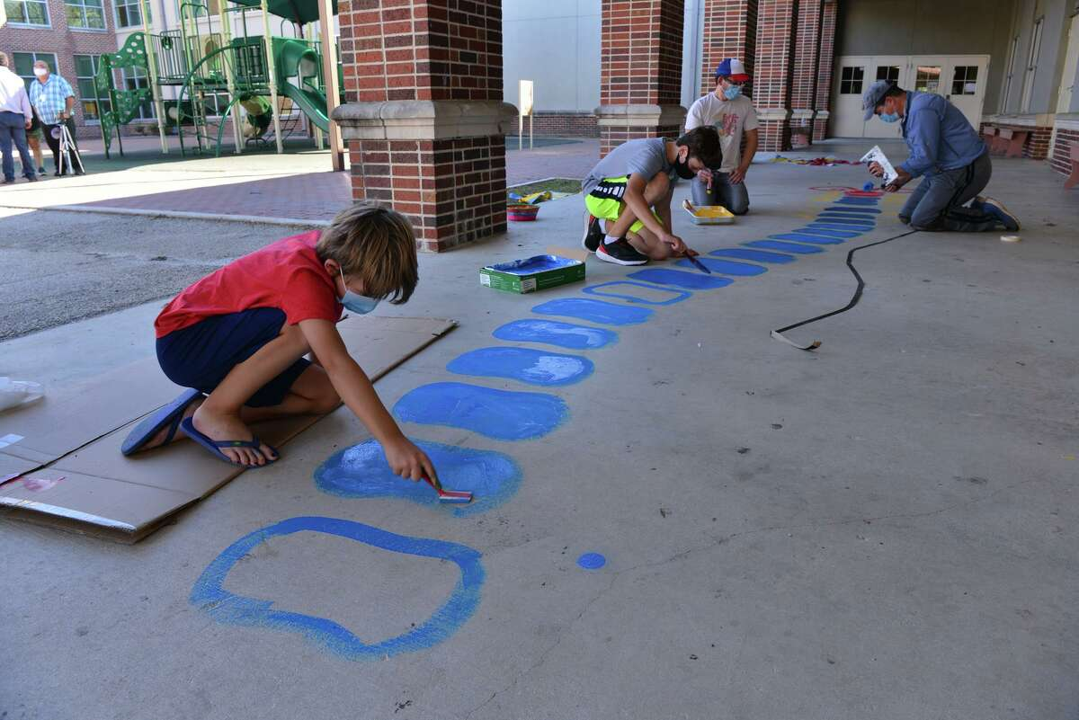 Campbell Evans and Tristen Hoffman paint the stencil of an alphabet-themed centipede in the courtyard of Twain Dual Language Academy on Sunday afternoon. It is the first of 10 outdoor beautification projects at SAISD schools spearheaded by the district's health and physical education departments.