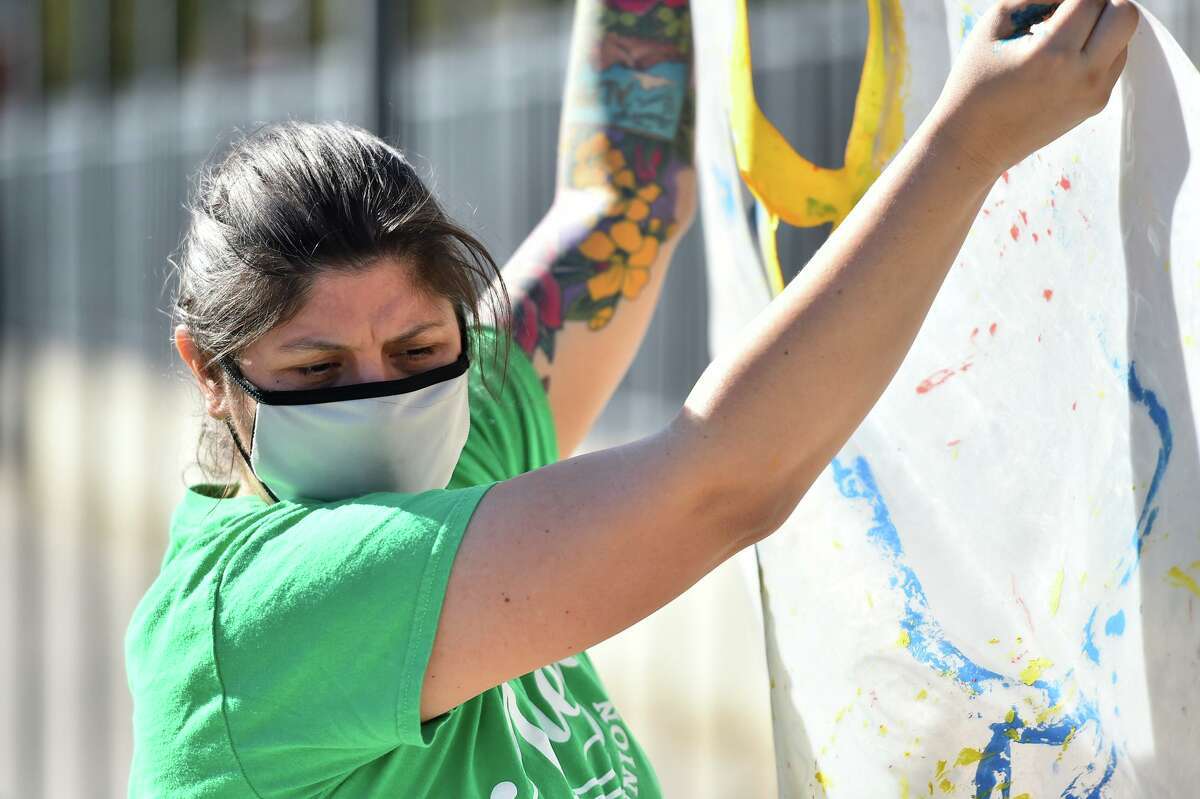 Cristina Noriega moves a stencil in the courtyard of Twain Dual Language Academy on Sunday afternoon. It is the first of 10 outdoor beautification projects at SAISD schools spearheaded by the district's health and physical education departments.