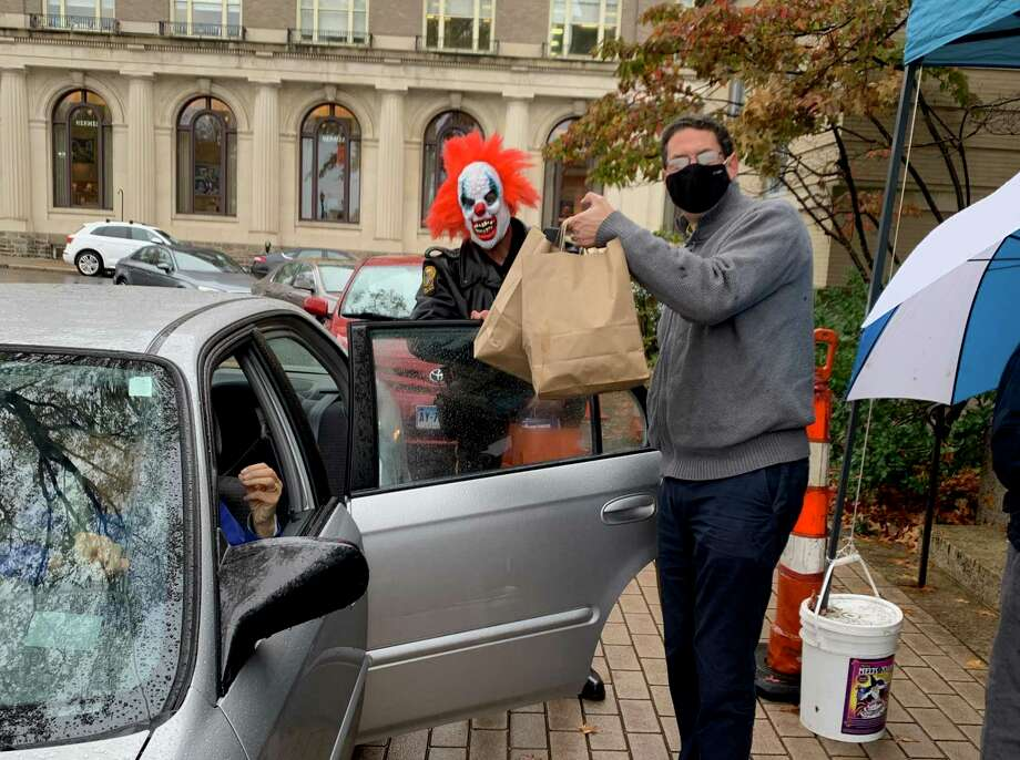 Greenwich Police Officer Dan Hendrie, wearing a Halloween mask, and CareFinders CT Executive Director Daniel Krause distribute lunches during the Teddy's Ready Drive-Thru Halloween Lunch for Greenwich Senior Center members on Friday, Oct. 30. Presented by the Greenwich Commission on Aging, senior center head chef Teddy Torchon and his staff served more than 150 hot lunches and distributed trick-or-treat bags full of candy and goodies from Commission on Aging sponsors. Photo: Contributed Photo / Contributed Photo / Contributed Photo
