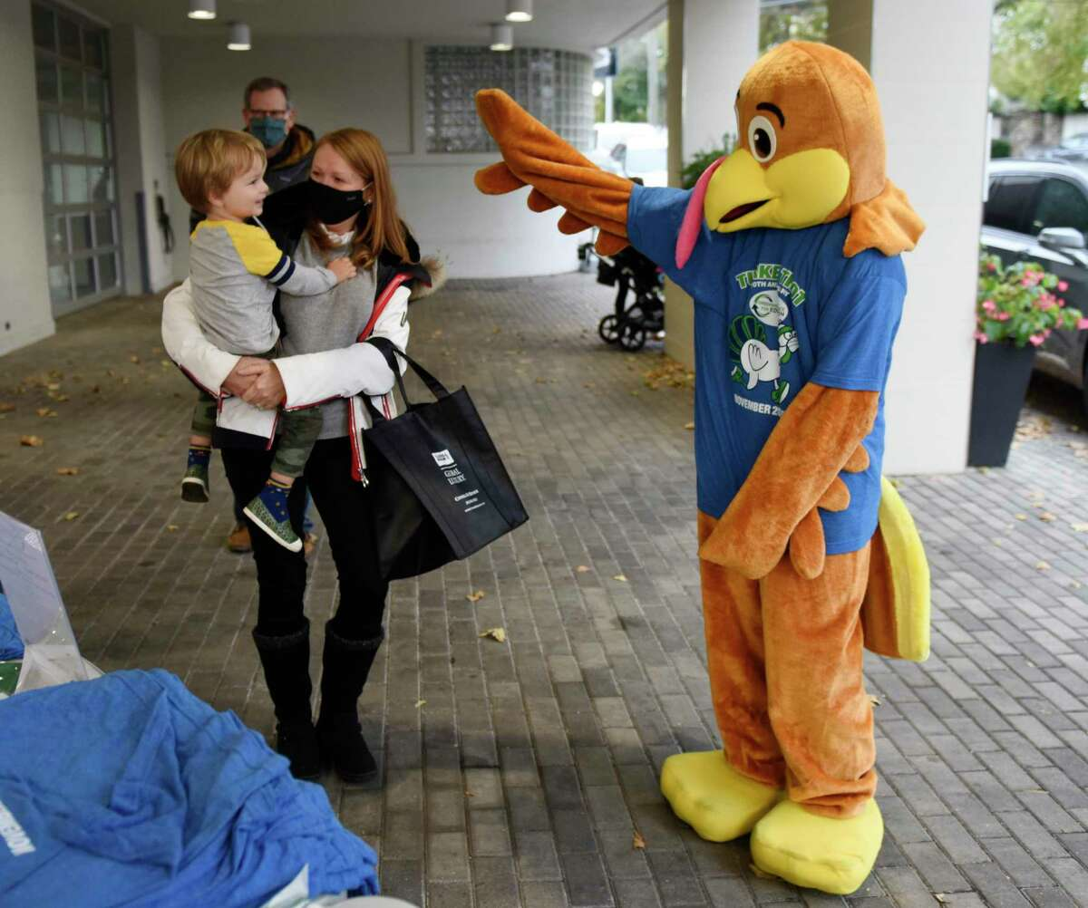Greenwich's Kimberly Gibbs and her son, August, 2, say hello to a turkey while signing up for the Greenwich Alliance for Education Turkey Trot Month-Long Fitness Challenge at Cadillac of Greenwich in Greenwich, Conn. Sunday, Nov. 1, 2020. The Turkey Trot, which typically draws more than 1,000 participants for a 5K race over Thanksgiving weekend, will be