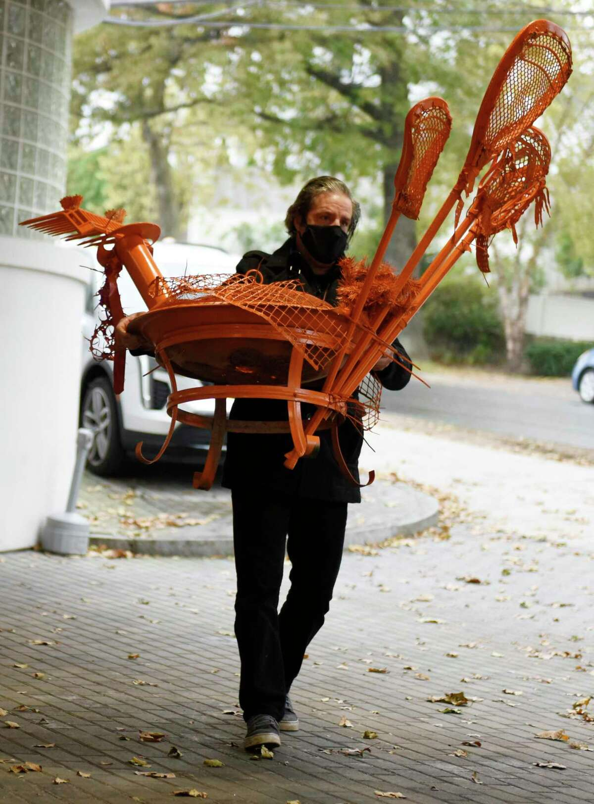 Artist Michael Manning carries one of his and Ben Quesnel's turkey sculptures to the sign up station for the Greenwich Alliance for Education Turkey Trot Month-Long Fitness Challenge at Cadillac of Greenwich in Greenwich, Conn. Sunday, Nov. 1, 2020. The tenth anniversary of the Turkey Trot 5K was reimagined this year as a month-long fitness challenge due to restrictions from the pandemic. The Turkey Trot, which typically draws more than 1,000 participants, is Greenwich Alliance for Education's largest yearly fundraiser. The group hopes to raise $50,000 this year to support programs at Greenwich Public Schools.