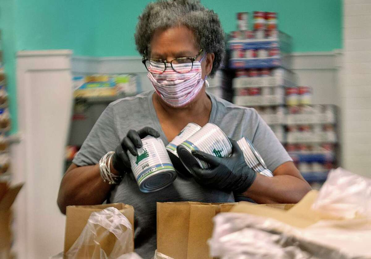 Volunteer, Marsha Royster, adds canned beef to bags at the Downtown Evening Soup Kitchen.