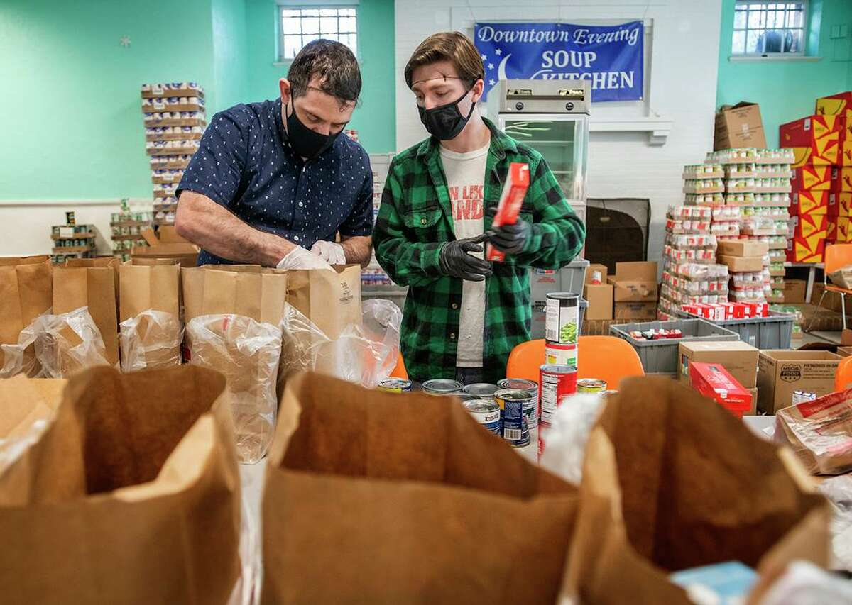 Volunteers Marcus Alexander (L) and Jack Goodman fill bags at the Downtown Evening Soup Kitchen.
