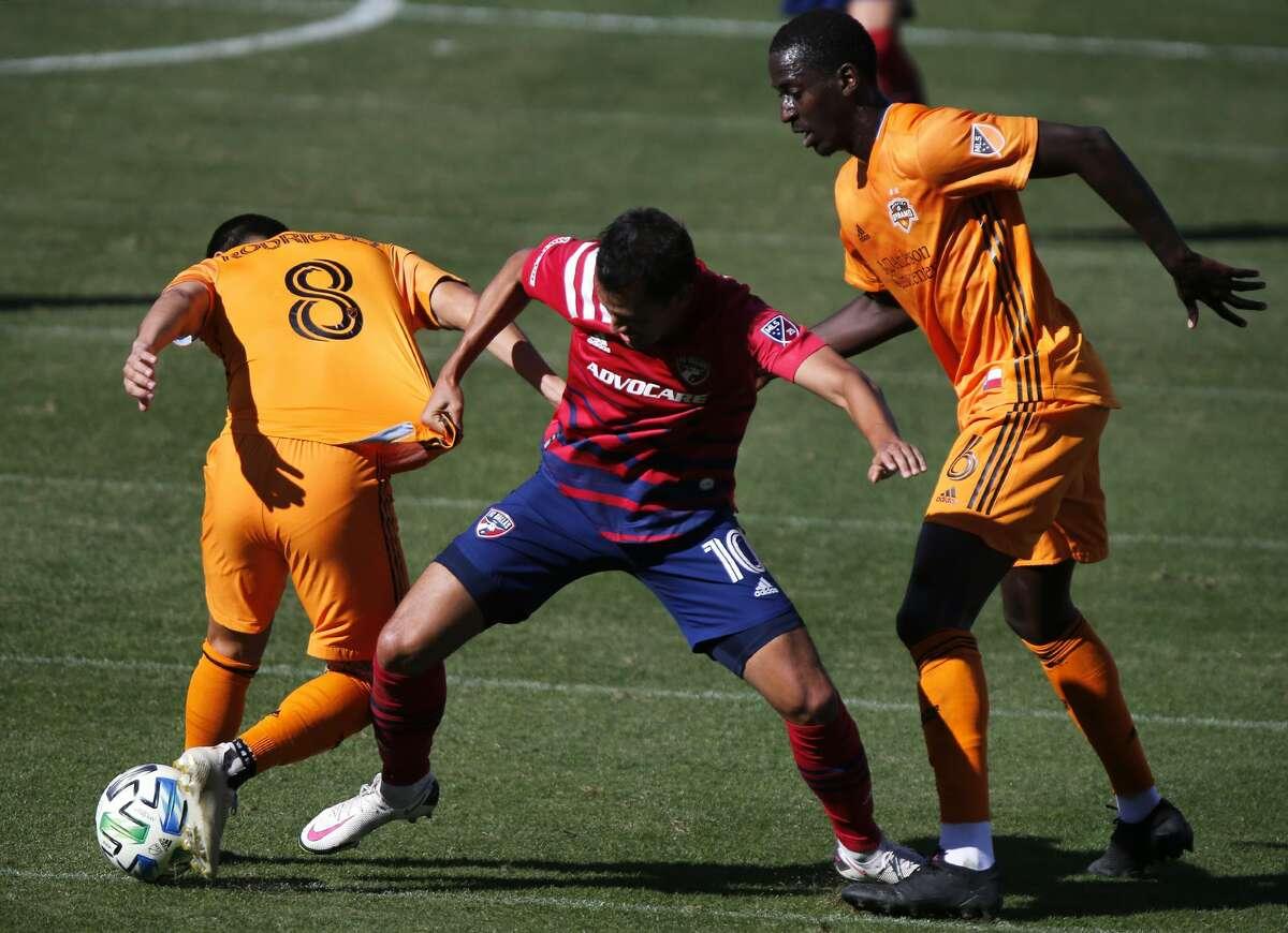 El mediocampista colombiano Andrés Ricaurte (10) lucha por la pelota entre Memo Rodríguez (8) y Wilfried Zahibo (6) durante la victoria del FC Dallas sobre el Houston Dynamo por 3-0 en Frisco, Texas, el sábado 31 de octubre de 2020.