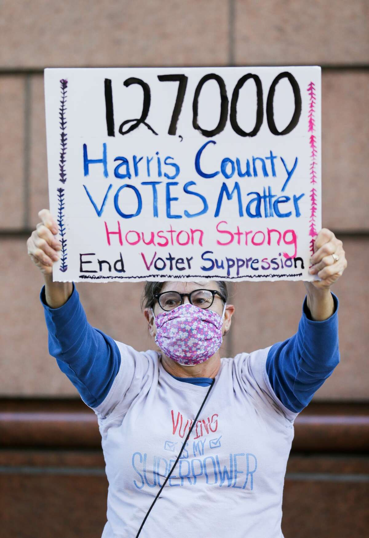 Gina Dusterhoft holds up a sign while being part of a group of demonstrators who gathered outside the Bob Casey Federal Courthouse to voice their support of drivethrough voting, which was available for early voters in Harris County, on Monday, Nov. 2, 2020, in Houston. Republicans politicians and activists filed a federal lawsuit in opposition to the voting method, which accounted for 127,000 votes.