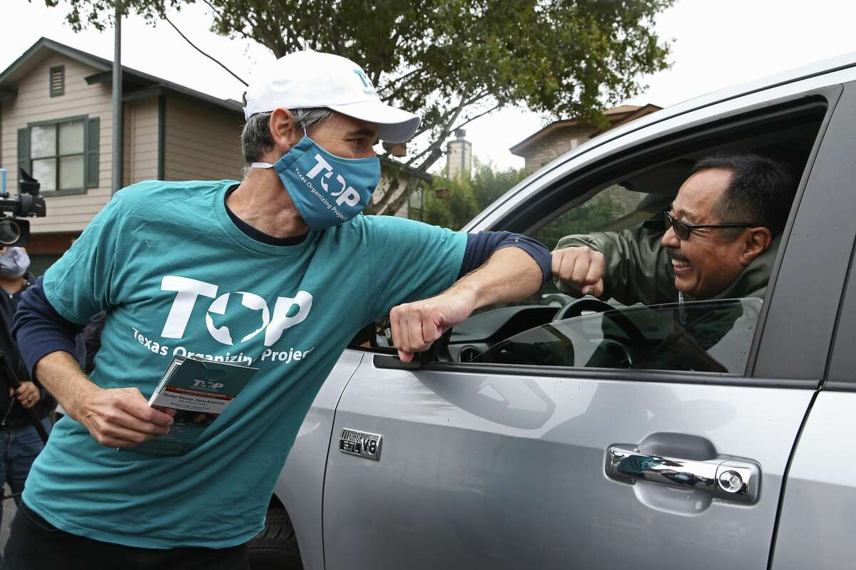 Former Texas congressman Beto O'Rourke, left, meets Phil Enano, while canvassing the Brookstone neighborhood for Texas House District 121 Democratic candidate Celina Montoya, Tuesday, Oct. 27, 2020.