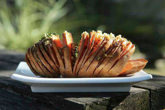 A finished Hasselback sweet potato with minced garlic and butter comes off the grill.
