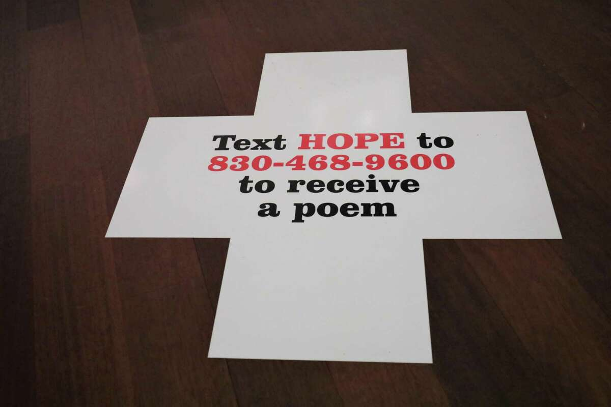 """Vinyl decals inviting visitors to text a number to receive a short poem by a local writer can be found throughout """"Robert Indiana: A Legacy of Love,"""" the fall exhibit at the McNay Art Museum."""