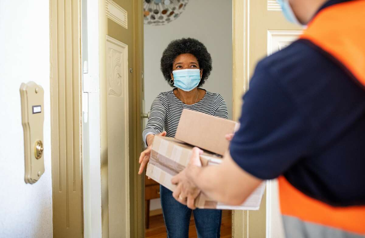 A woman getting a package from a delivery person during the pandemic.