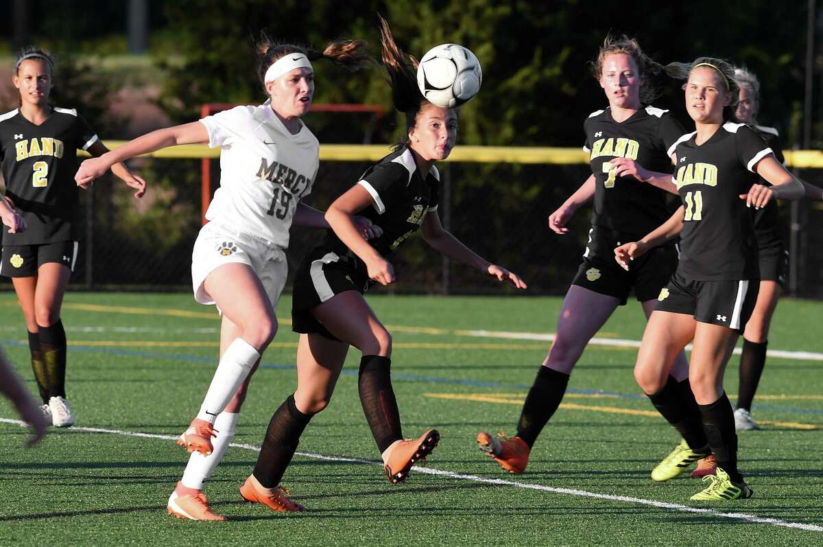 Kaila Lujambio (left) of Mercy and Lily Freid (center) of Daniel Hand go after a loose ball in the first half in Madison on September 17, 2019.