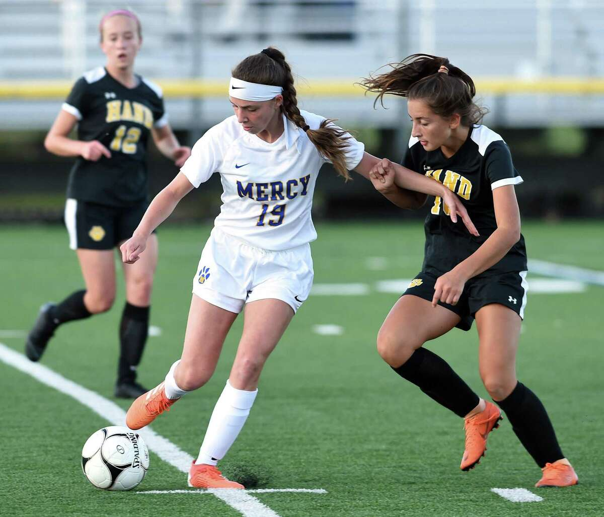 Kaila Lujambio (left) of Mercy and Lily Freid of Daniel Hand fight for the ball in the first half in Madison on September 17, 2019.