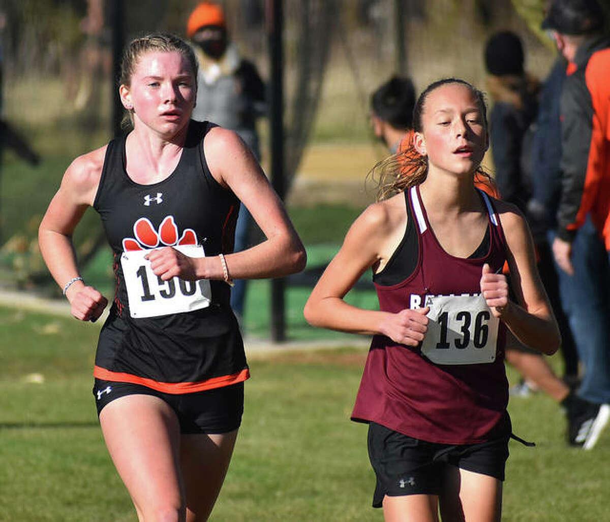 Edwardsville sophomore Riley Knoyle, left, runs alongside Belleville West's Alyssa Elliott during the Class 3A Normal Community Sectional on Saturday.