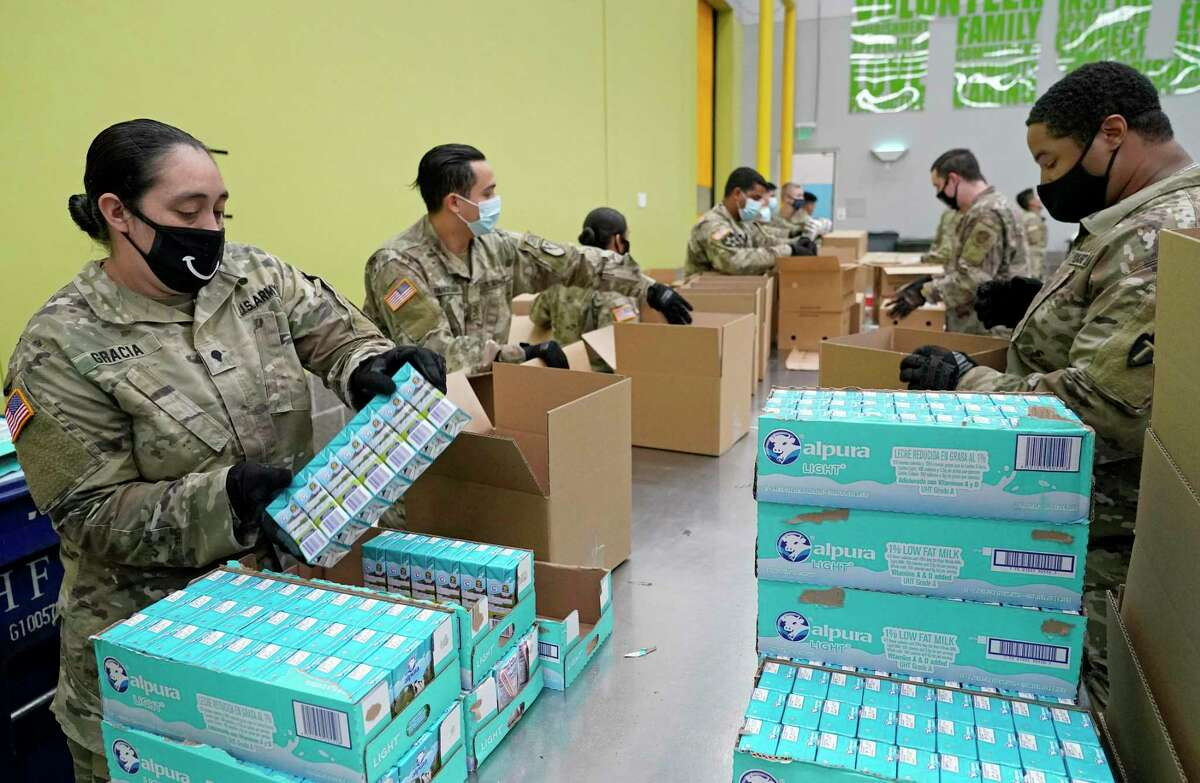 U.S. Army National Guard Spc. Katty Gracia, left, and Pfc. Jemal Watler, right, and others pack boxes at the Houston Food Bank in July 2020. The Houston Food Bank, the nation's largest food bank, serves 18 counties in southeast Texas, and in June alone delivered more than 27 million pounds of food during the coronavirus pandemic.