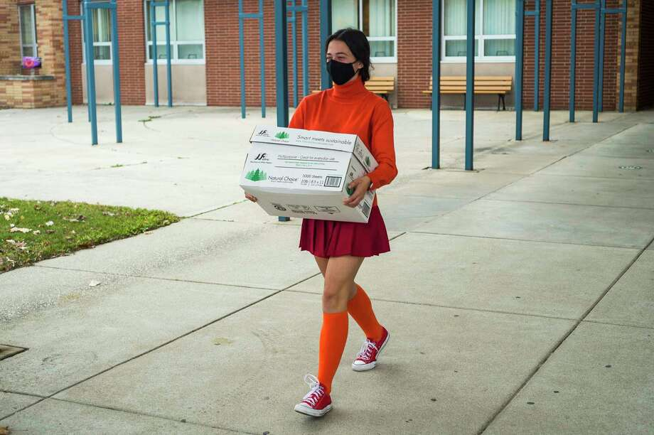 Bullock Creek High School senior Rita Gorsuch carries boxes of books out to a vehicle for them to be donated to Windover High School, as the result of a book drive organized for the annual Creekers for a Cause effort, Friday, Oct. 30, 2020 at Bullock Creek High School. (Katy Kildee/kkildee@mdn.net)