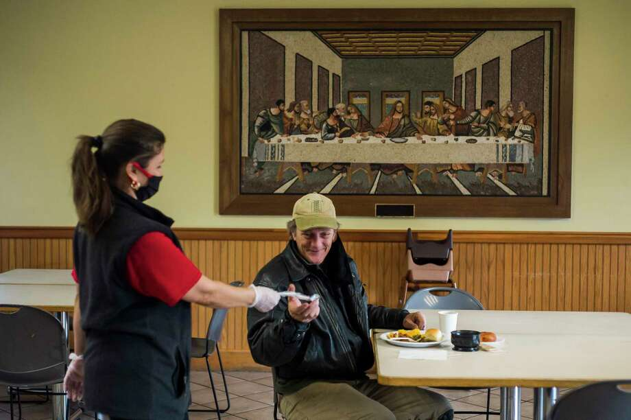 Victoria Bantau, left, hands silverware to John Schroeder, right, as Midland's Open Door reopens its dining hall for their daily soup kitchen service Monday in Midland. Hot meals are still being offered to-go from the front porch as well. (Katy Kildee/kkildee@mdn.net)