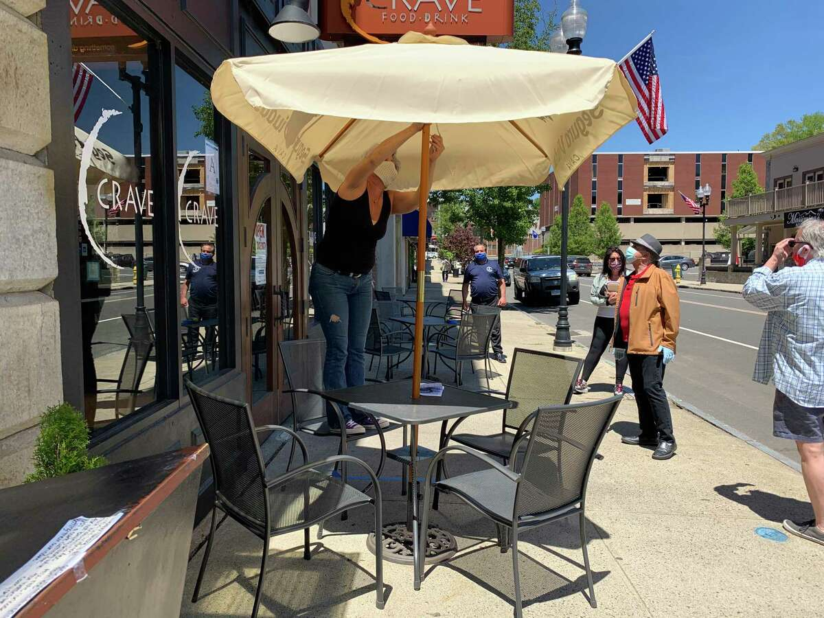 The popular Crave restaurant on Ansonia's Main Street will be closed until at least Nov. 7 because an employee tested positive for COVID-19. Here Libby Meissner prepares an outside dining table when the restaurant in preparation for a reopening this spring.