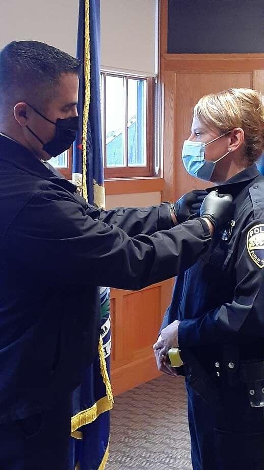 Chief Josh Glass adds brass to Det. Sgt Kirsten Goodspeed's uniform marking the change in her rank. Photo: Courtesy Photo