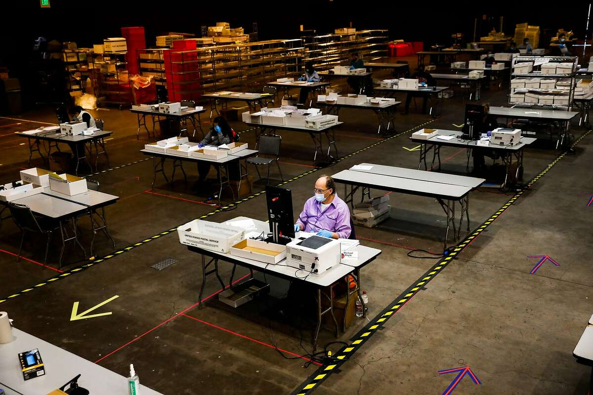 Michael Doyle (center) works on processing early ballots the day before election day at the Bill Graham Civic Auditorium.