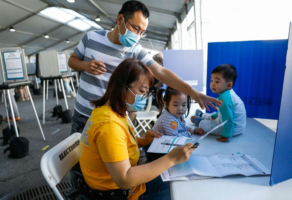 Lily Wong reviews her ballot as she votes in San Francisco with husband Hai Wong and their children Royce, 2 (right), and Stacy, 4.