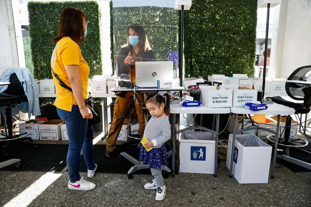 Lily Wong (left) stands with daughter Stacy Wong,4, as she prepares to vote ahead of Election Day in a tent at Civic Center on Monday, Nov. 2, 2020 in San Francisco, California.