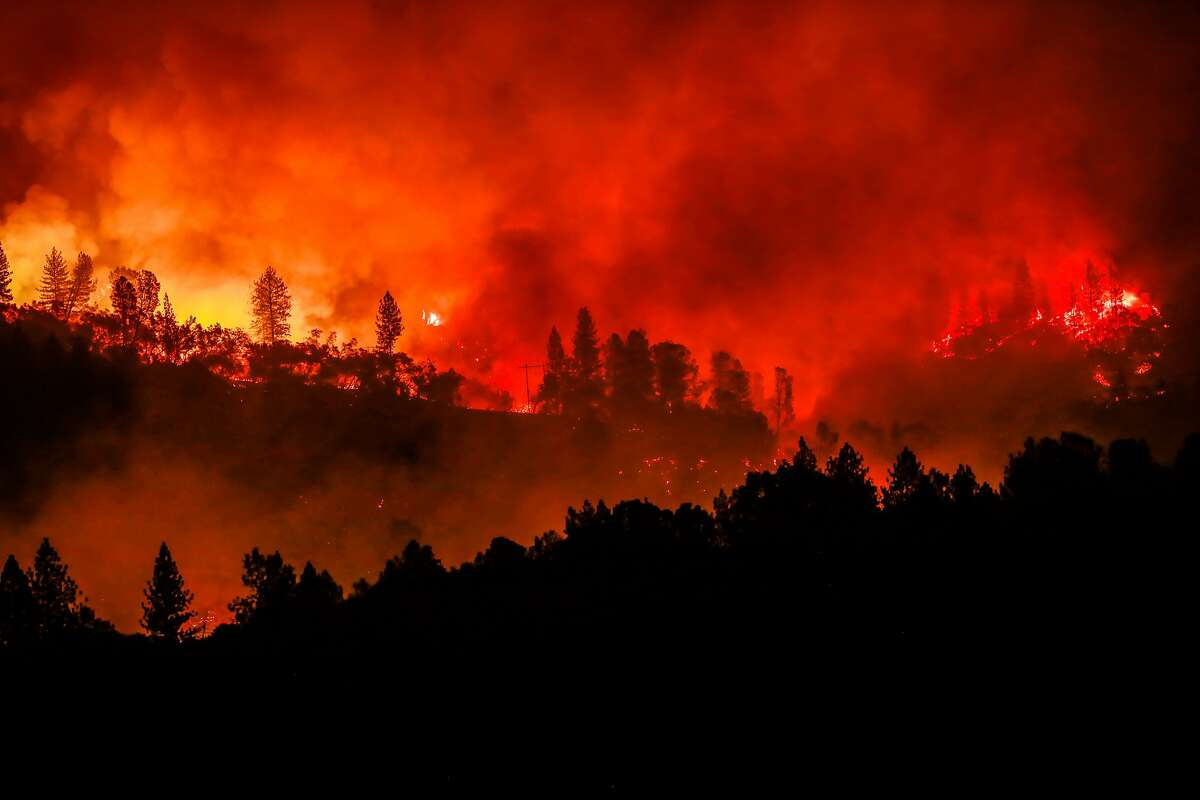 The Camp Fire, which devastated Butte County, burns along a ridgetop in 2018. Victims of that fire, which was caused by PG&E equipment, can start receiving funds from a trust soon.