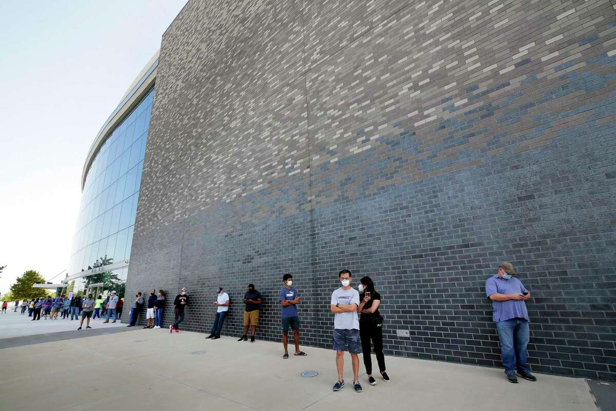 Voters wait in line outside of the Smart Financial Center as early voting begins Tuesday, Oct. 13, 2020 in Sugar Land, TX.