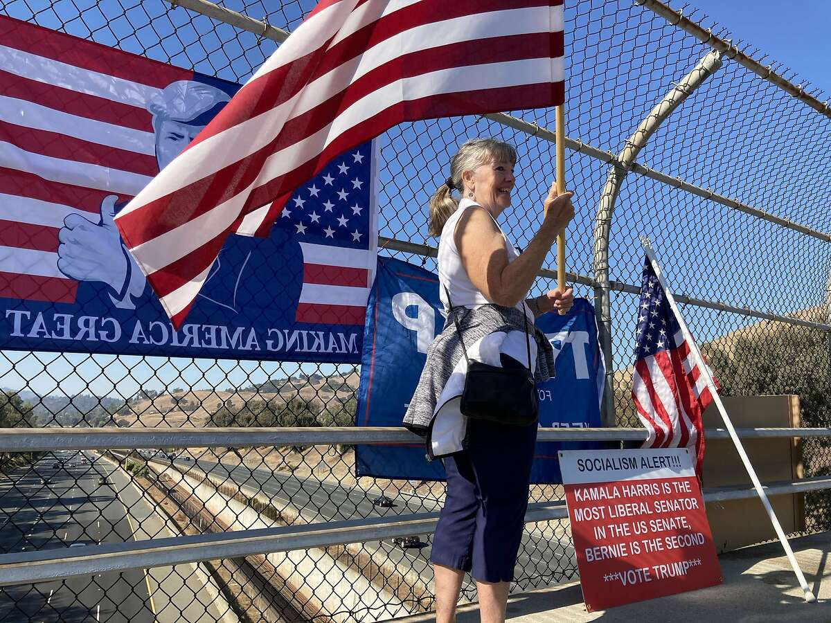 Chris Bratton,65, of Walnut Creek, waves a flag in support of Donald Trump on an overpass above Highway 24 Monday.
