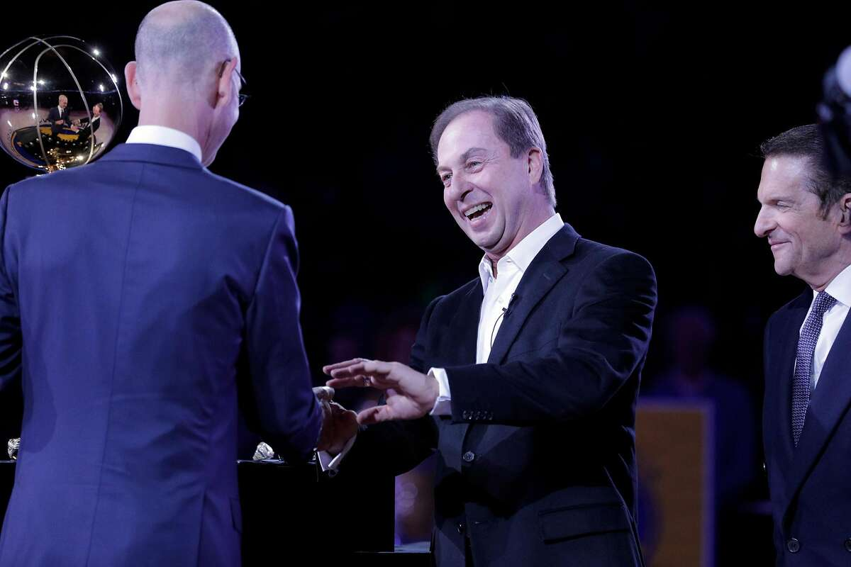 Warriors owner Joe Lacob smiles as he recieves his championship ring from NBA Commissioner Adam Silver before the Golden State Warriors played the Oklahoma City Thunder at Oracle Arena in Oakland, Calif., on Tuesday, October 16, 2018. The Warriors received their 2018 NBA Championship rings and saw their championship banner raised in the arena