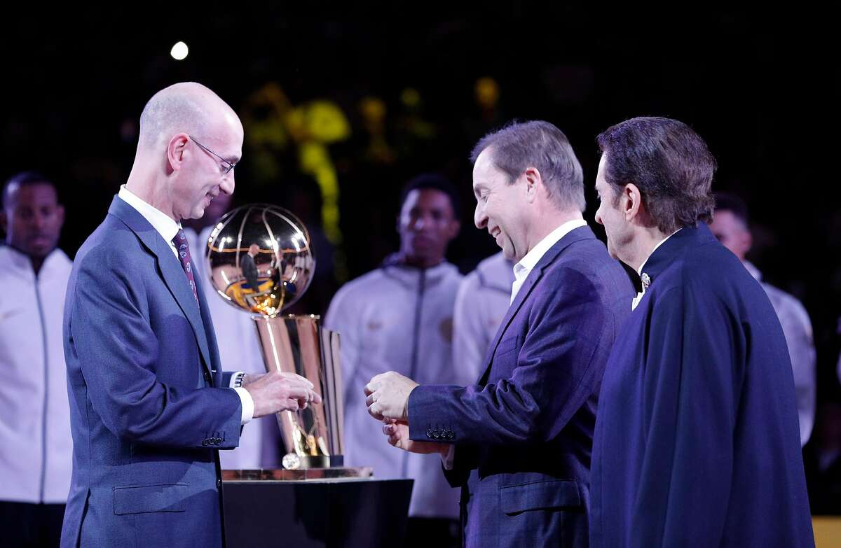 Warriors owners Joe Lacob (center) and Peter Guber get their championship rings from NBA Commisisoner Adam Silver.